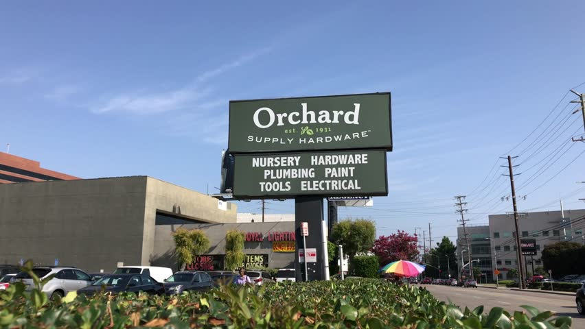 LOS ANGELES, Sep 1, 2018: Close up of an OSH Orchard Supply Hardware store sign and logo next to a West LA store against a blue sky with plants in foreground. The chain is set to close in October.