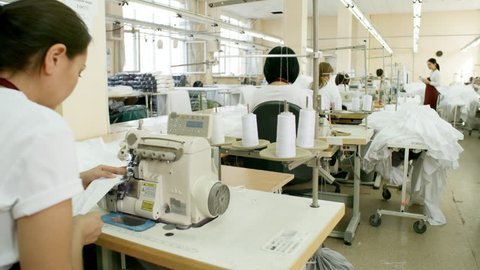 Female workers using sewing machines while working in textile factory; Asian supervisor using digital tablet