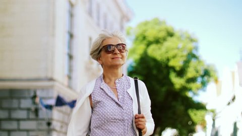 old age, retirement and people concept - happy senior woman walking along city street in summer