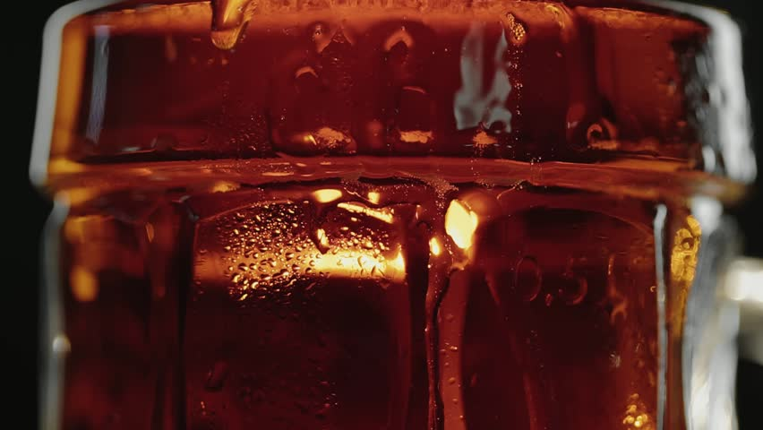 Sweaty mug of cold dark kraft beer, drops flow down the glass, in bar or pub. Close up panorama shot. Isolated black background. Slow motion