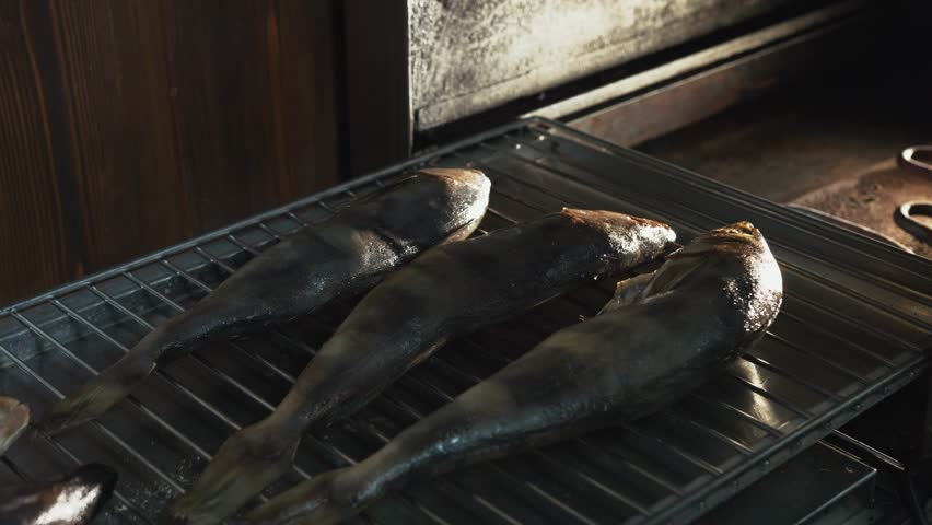 Salt fish lying on grill or grate placed in smokehouse or smoke oven for smoking. Restaurant or cafe, kitchen, close up | Shutterstock HD Video #1015915240