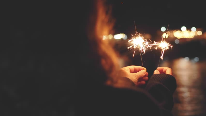 A young red-haired woman stands at the seaside on the pier and holds burning lit Christmas bengal lights and meets the new year against a bright background of bokeh large lights | Shutterstock HD Video #1015950580