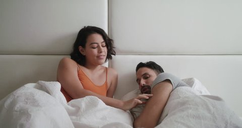 Wife trying sexual approach to bored husband in bed. Angry man refusing to have sex with woman and going back to sleep. Relationship problems for married people at home