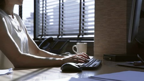 Dolly shot of businesswoman working at desk in office