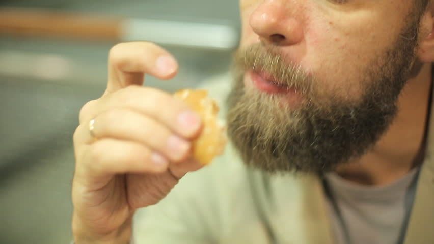 Bearded Caucasian man sitting in the evening at a table in a summer cafe and eating a hamburger. close up. | Shutterstock HD Video #1016034340