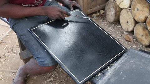 African Artifacts. A man makes patterns on polished wooden boards in a market.