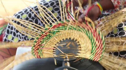 African Art. A woman weaves a fan in an art marketplace in Ghana.