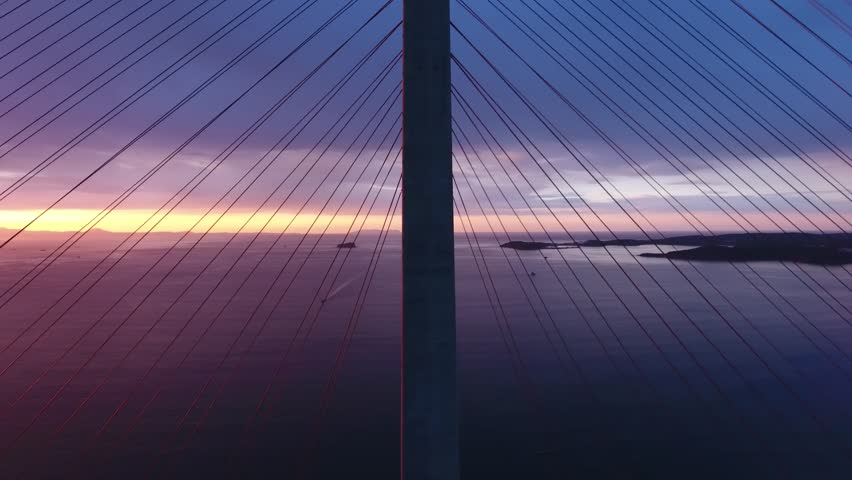 Epic sunrise above Russkiy island bridge longest cable. Abstract graphical pylon . Dramatic tension stormy sky.  Best of Russia. Aerial drone cinematic 4k | Shutterstock HD Video #1016097610
