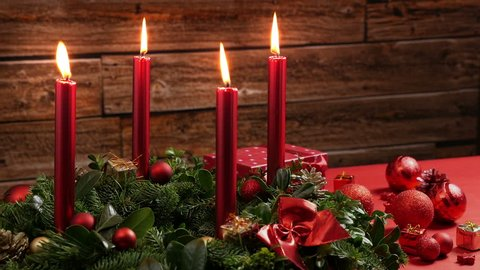 Four burning red candles on a traditional advent wreath of green fir twigs and mistletoes with festive decoration in front of a rustic wooden wall, close-up real time shot with copy space, nobody