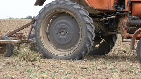 Old tractor plowing field. Farmer plowing the field, close-up. The old rusty tractor preparing land for sowing. Slow Motion in 96 fps.