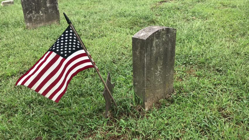 American flag blowing in the breeze next to a grave stone on the grass in a cemetery.