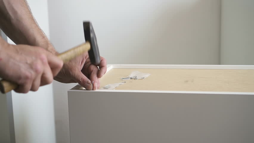 Furniture assembler driving nails into shelves. Technologist using hammer in his hands to assemble house decoration. Indoors. | Shutterstock HD Video #1016122030