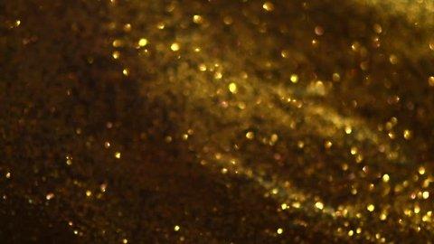 Glitter golden sparkles background. Gold Glitter Dust backdrop. Christmas golden light shine particles bokeh. Holiday concept. 4K UHD video