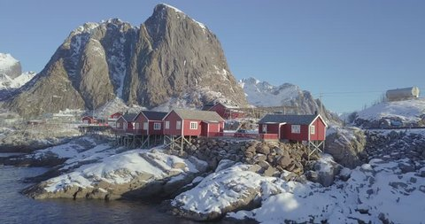 Aerial drone footage of amazing Lofoten Islands winter wonderland scenery with traditional red Rorbuer cabins on a sunny day with blue sky, village of Hamnoy, Lofoten archipelago, Norway, Scandinavia.
