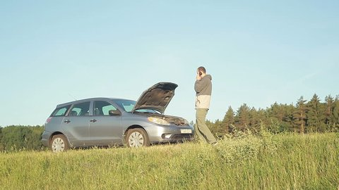 Man with broken down car on side of road