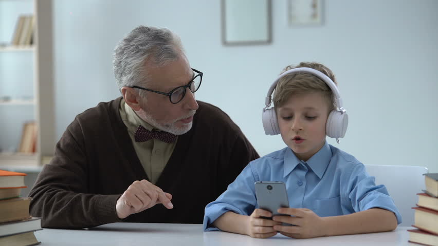 Senior man criticizing grandson, boy in earphones ignoring him, generation gap | Shutterstock HD Video #1016162380