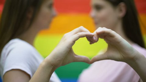 Lesbians showing love sign, kissing on rainbow flag background, minority right