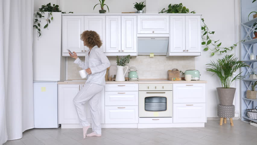 Young Woman Dancing And Using Cellphone In Kitchen. | Shutterstock HD Video #1016210140