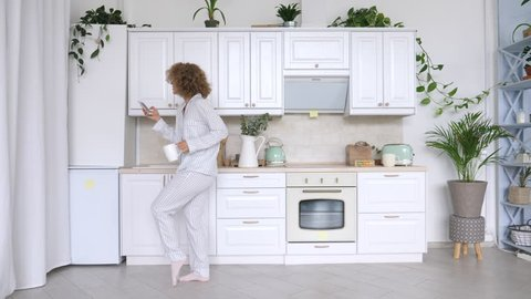 Young Woman Dancing And Using Cellphone In Kitchen.