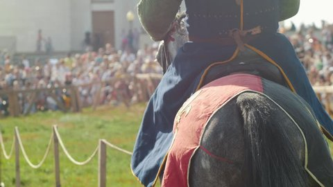 Athletic men in historical costumes on horseback at a jousting tournament. The audience is watching. Festival of the middle ages. Summer.