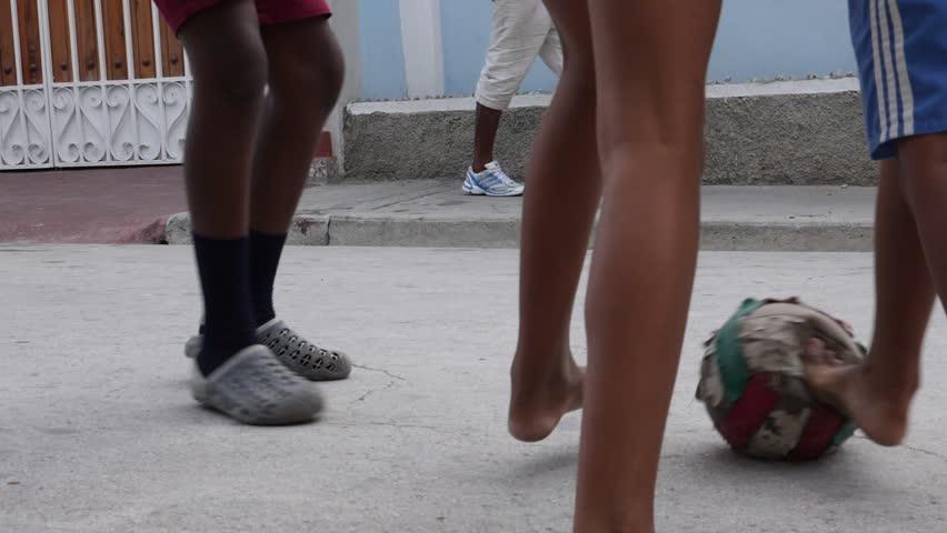 Santiago de Cuba / Cuba - July 17 2018: Poor Kids Play Football Soccer On The Old Street Santiago de Cuba