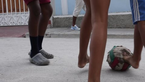 Santiago de Cuba / Cuba - July 17 2018: Poor Kids Play Football Soccer On The Old Street Santiago de Cuba