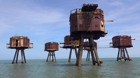 CIRCA 2018 - The Maunsell Forts, old World War two structures stand rusting on stilts in the Thames River Estuary in England.