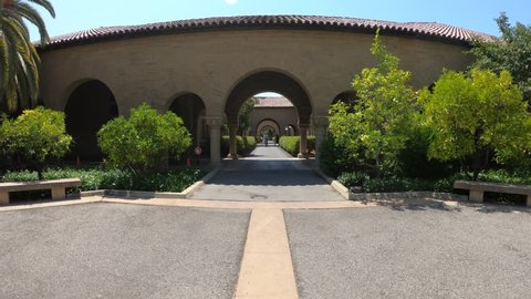 Palo Alto, California, United States - August 13, 2018: Main Quad archway at Stanford University Campus in Silicon Valley with students moving by bicycle.