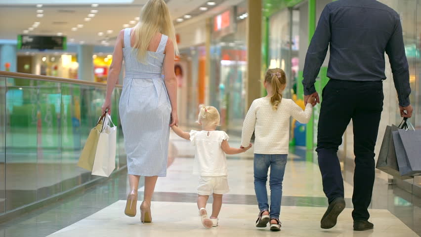 Happy family of four doing shopping. Family in mall. Children at mall with parents. Family shopping in big store. Family walking through shopping mall carrying sale bags. shopping girl bag slow-motion