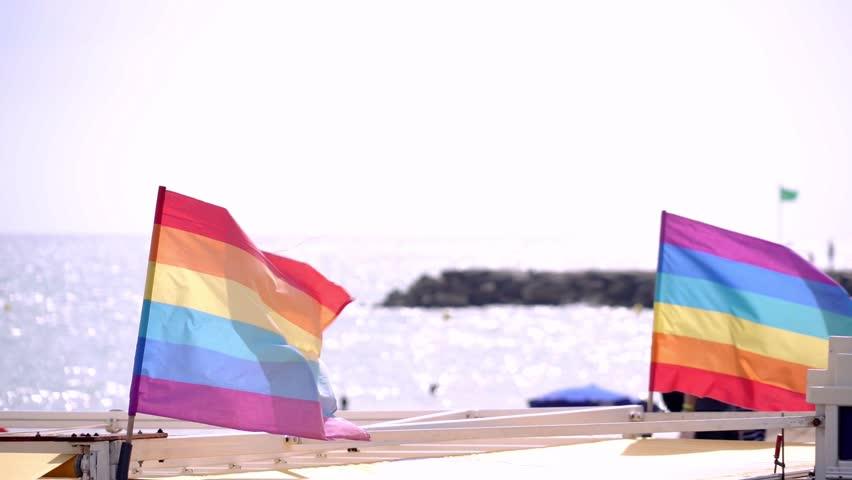 Slow motion gay pride flag blowing in the wind on Sitges, in Barcelona province. Perhaps Spain top gay destination, with LGTB events like Gay carnival, pride and Gay Spring break. Slowmotion from 120  | Shutterstock HD Video #1016257690