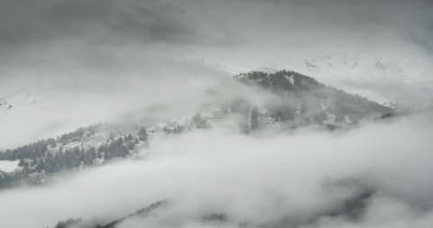timelapse footage of dark clouds moving across a cold winter landscape in the tyrol region of austria show white snow landscape and alpine forest