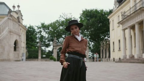 Attractive mulatto curly woman in boho style look seductively walks through the ancient city square. Catwalk, new collection, fashion campaign. vintage concept. Female portrait, slow motion