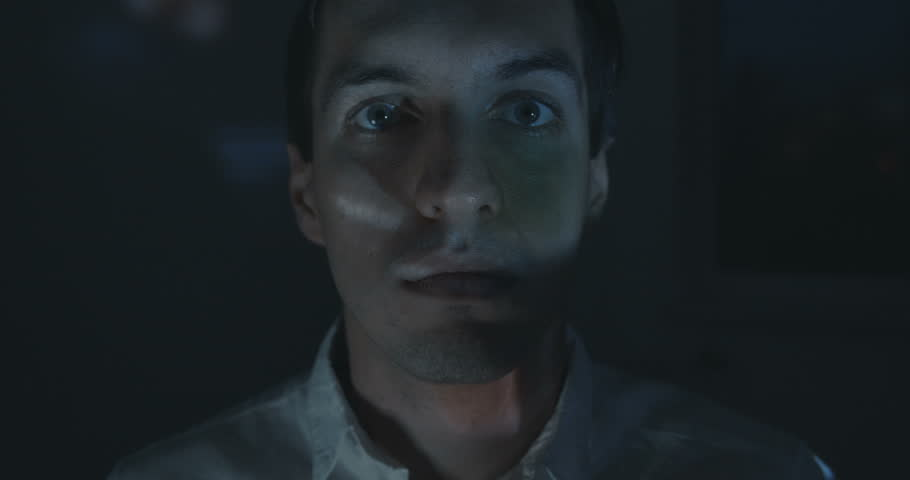 Close up of young man watching a video or film on TV or a computer monitor at home. Reflection on his face. Timelapce
