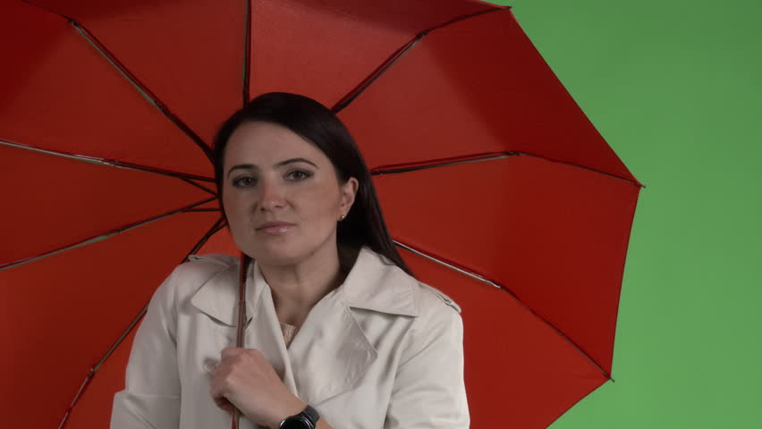 Brunette woman under red umbrella against green screen closeup | Shutterstock HD Video #1016308270