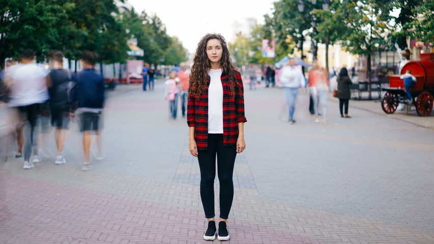 Time-lapse of attractive young woman standing in city center on busy street looking at camera wearing casual clothing while crowds of people are passing by.