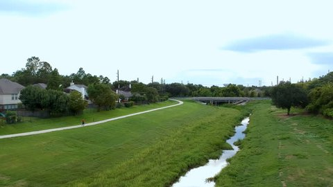Aerial dolly of a large retention pond and drainage canal that is part of flood control for a large suburban area with a person walking on the biking trail that runs adjacent to it.