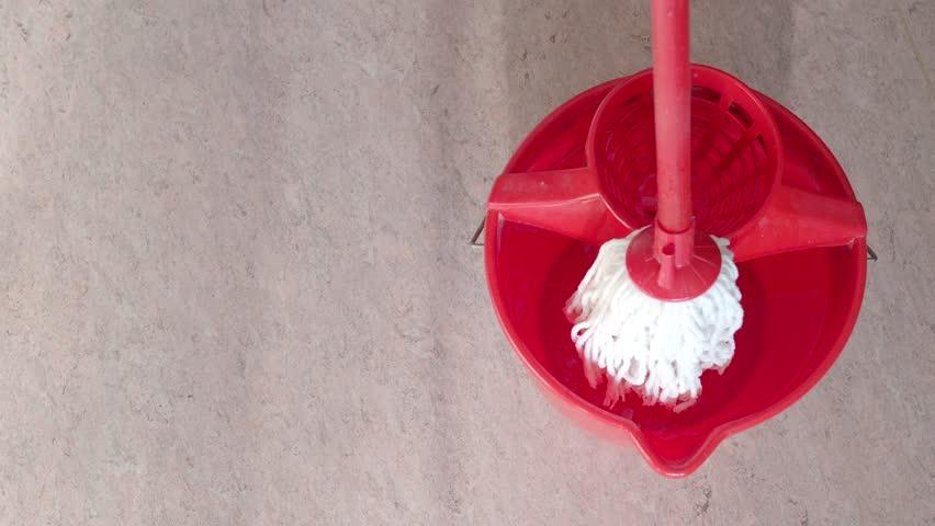white cotton mop cleans pink linoleum floor near red bucket with water