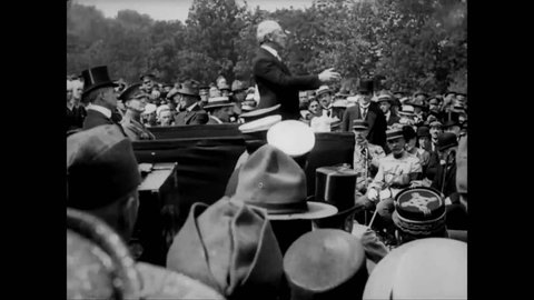 CIRCA 1919 - President Wilson makes a speech at a military cemetery in Suresnes, France; Admiral Grayson, and Marshal Foch join him in laying wreaths.