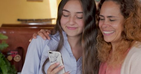 Genuine moment of a happy latino mother and teenage daughter taking selfies and being affectionate and then looking at their cell phone together