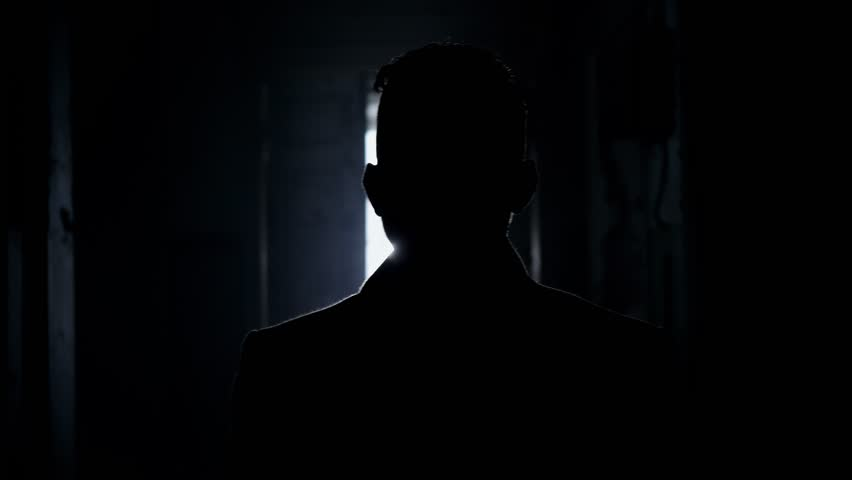 Silhouette of mature short haired man dressed in long coat with straight collar walking along dark corridor towards empty bright room with white dusty walls and big arched windows.