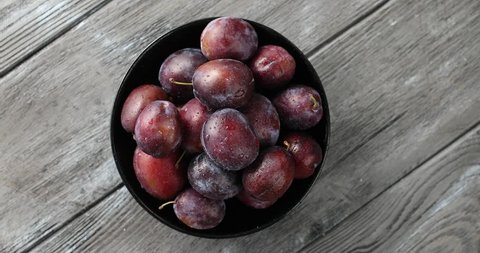 Top view of round bowl filled with ripe wet purple plums and served on gray wooden table