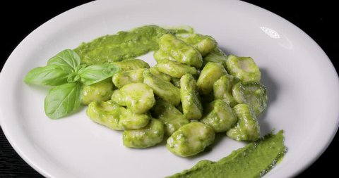 Vegetarian green potato gnocchi with fresh basil pesto arranged on a rotating plate.