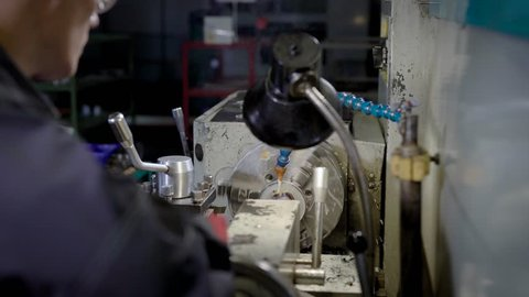 turner is working with turning machine in a workshop of industrial plant, processing metal detail