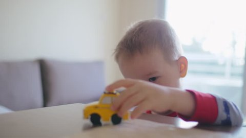 Portrait of cute boy playing with yellow car on table Child development in playful way. Child learns rules of road