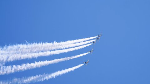 Five airplanes flying on the background of blue sky and leaving a condensation trail. 4K