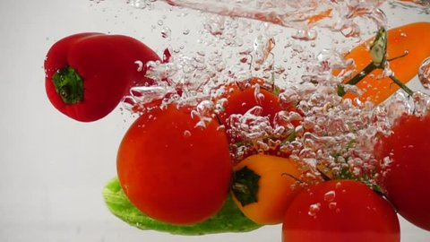 Array fresh vegetables, cucumber, pepper and tomatoes dropping in water, slow motion close-up