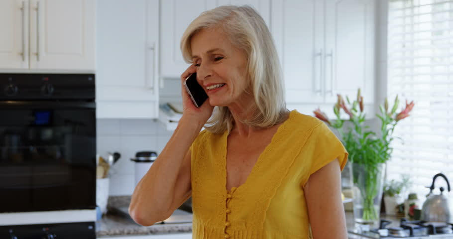 Senior Caucasian woman talking on mobile phone in kitchen at home 4k