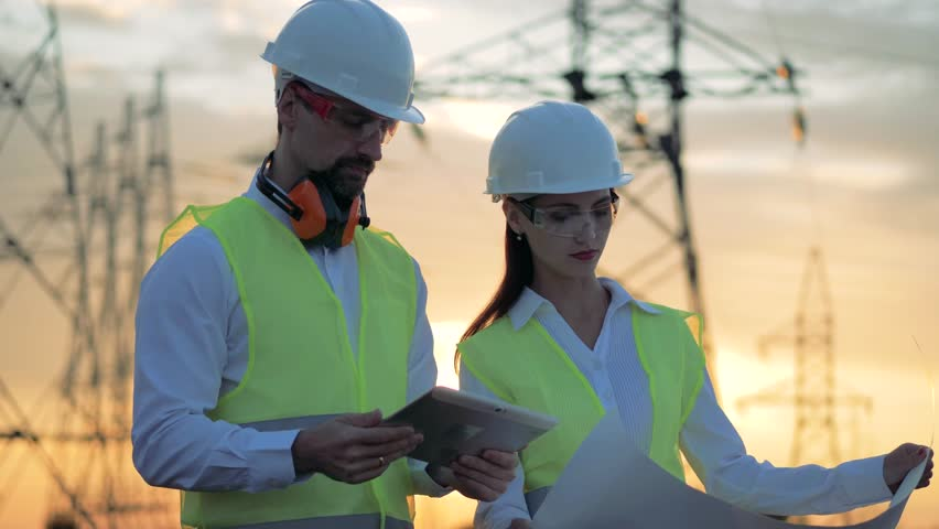 Professional electricians near transmission lines, close up.