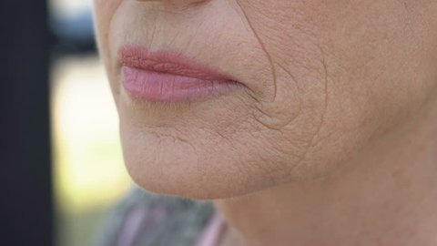Aged woman touching her wrinkled skin, nostalgic memories, anti-aging cosmetics