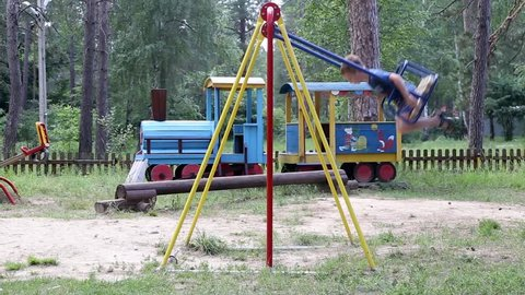 Boy on the Playground swings. The boy sits on a swing and shakes himself. Side view.